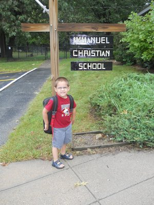 boy with backpack under the preschool's sign