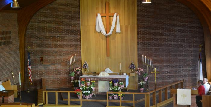 Easter flowers and plants surround the altar.